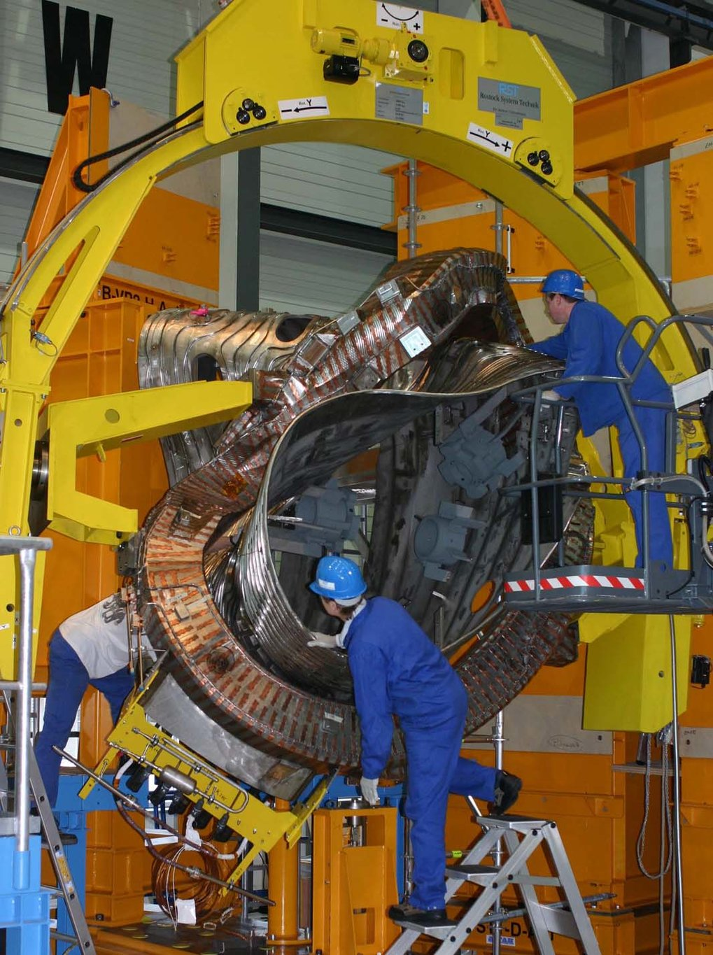 One of the 50 non-planar magnet coils of Wendelstein 7-X – about 3.5 metres high and weighing six tons – is being strung onto the plasma vessel.